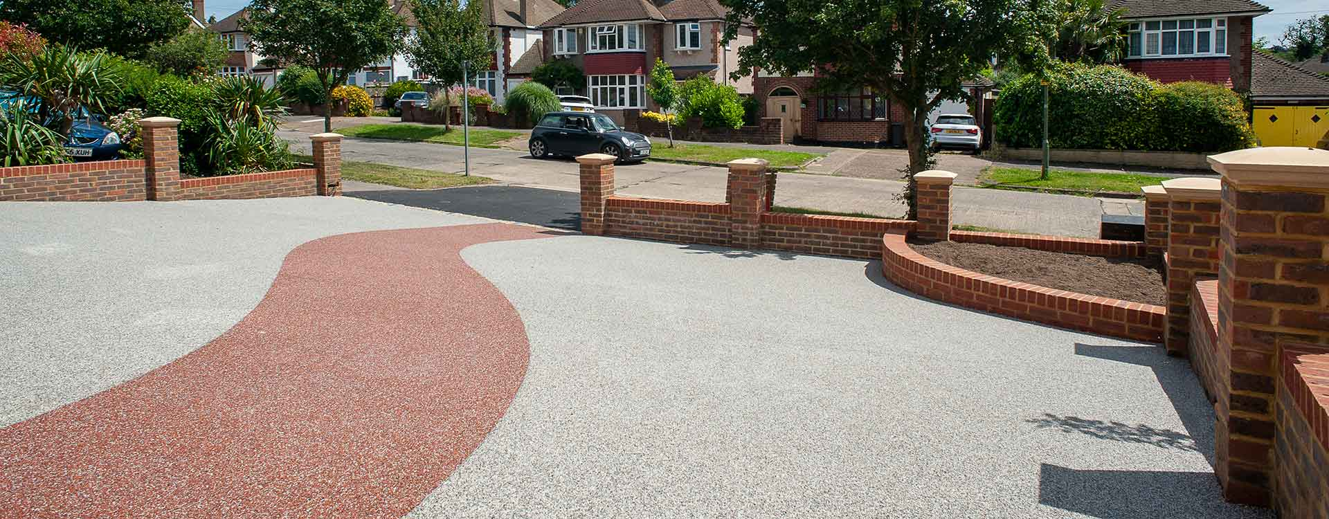 Grey resin driveway with brick wall