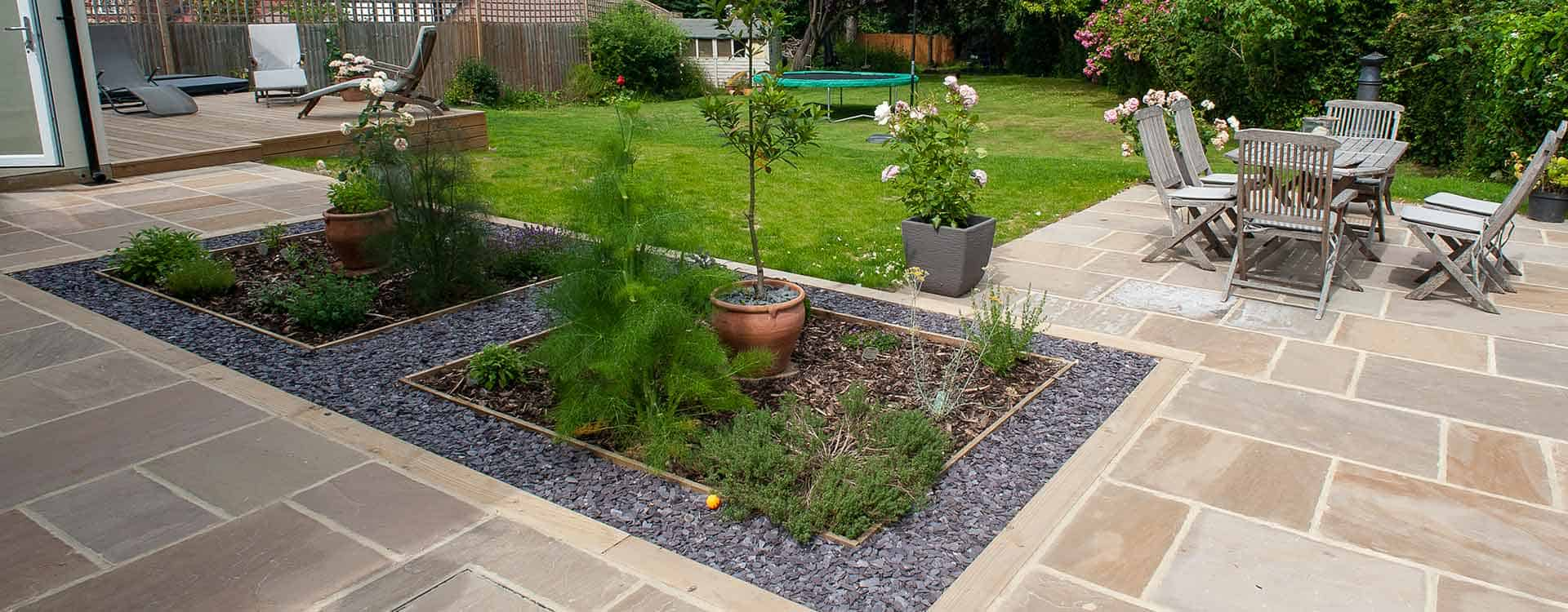 New sandstone paved patio with bedding plant area inset