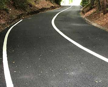 Newly laid asphalt private road with white lining