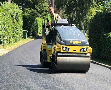 Roller flattening newly laid tarmac for a private road in Camberley Surrey