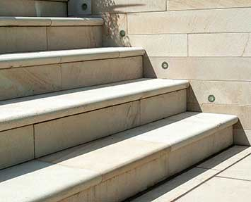 Stone steps with inset lighting leading down to garden
